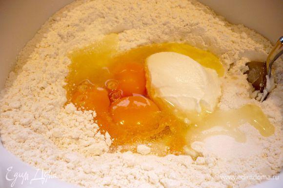 Для начала приготовим тесто. Муку просеиваем с содой и солью, делаем в ней углубление, всыпаем сахар, вбиваем яйца и, добавляя по ложке сметану, начинаем замешивать тесто. Когда мы смешали все ингредиенты и тесто стало более менее однородным, выкладываем его на рабочую поверхность и, понемногу добавляя муки, месим до эластичного мягкого состояния, когда тесто начнет отставать от рук.