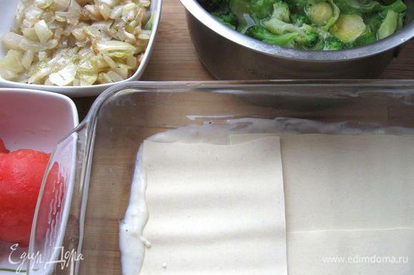 Форму смазать маслом. На дно формы положить часть соуса бешамель, разровнять. Положить листы лазаньи немного внахлест.