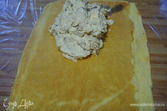 Тесто вынуть из духовки вместе с пергаментом и перекинуть на подготовленную заранее пищевую плёнку в размере большем, чем поверхность теста.
