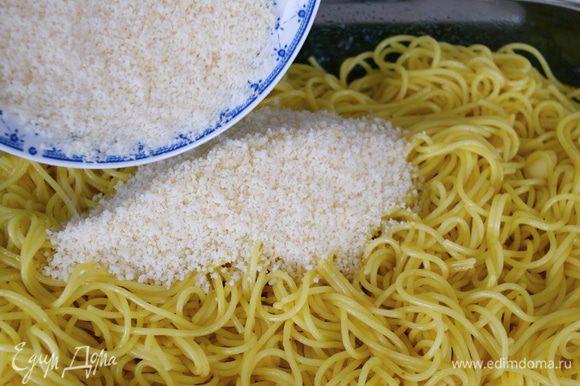 Твердый сыр мелко натереть и добавить к спагетти, снова размешать.