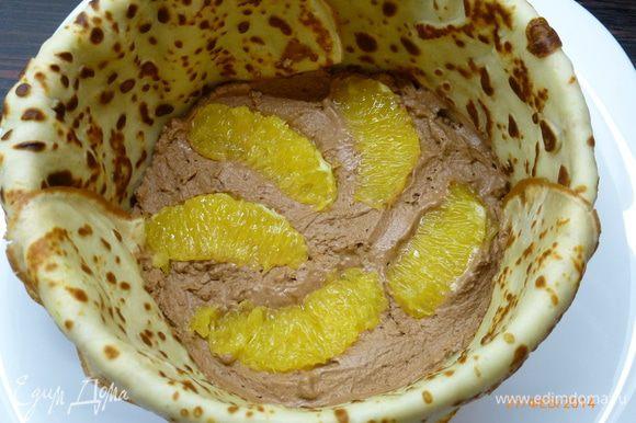 Выкладываем часть крема, вдавливаем в крем несколько долек апельсина.