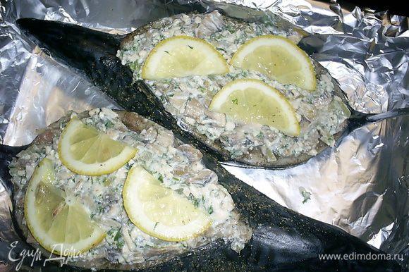 Полученной начинкой фаршируем рыбку, половинки кусочков лимона выкладываем сверху на начинку. Форму для запекания выстилаем фольгой и выкладываем рыбку спинкой вверх.