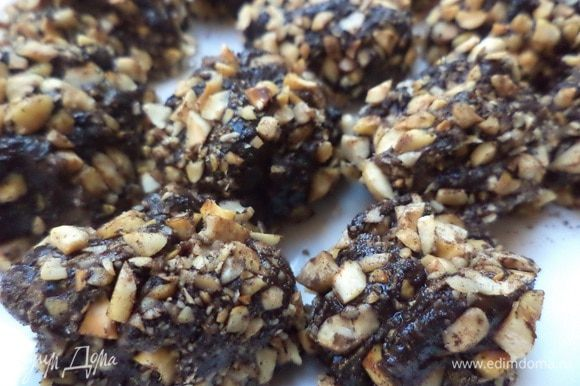 С помощью ложки, смоченной в холодной воде, сформировать из остывшей массы небольшие шарики. Обвалять шарики сначала в какао, затем - в рубленых орехах. На 2 - 3 часа убрать в холодильник.