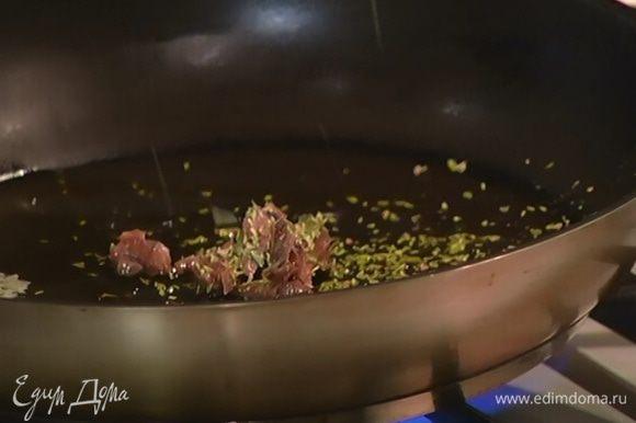 Разогреть в сковороде сливочное и оливковое масло, выложить анчоусы, посыпать орегано и обжарить на слабом огне.