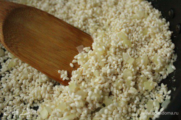Добавить к луку рис и, постоянно помешивая, дать рису стать полупрозрачным.