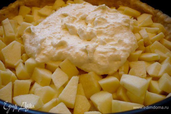 Теперь на тесто выложим половину яблок. Сверху выложим чуть меньше половины сливочной заливки, распределим заливку по яблокам.