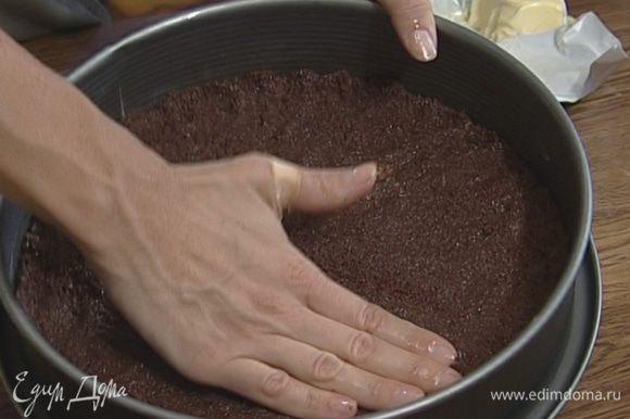 Разъемную форму для выпечки смазать сливочным маслом, выложить тонким слоем печенье с маслом и поставить в разогретую духовку на 10 минут.