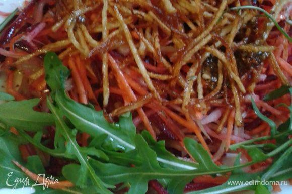 Свеклу, сельдерей, яблоко и морковь смешать, сверху выложить жареный картофель полить заправкой. Украсить руколой.