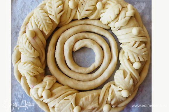 Готовое тесто разделить на 2 части. Из одной части раскатать прямоугольный пласт 60 на 15 см, выложить начинку, слепить края и свернуть в кольцо.