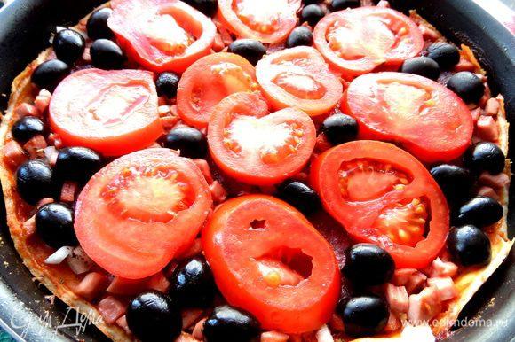 Оливки разделить пополам и щедро выложить на пиццу.