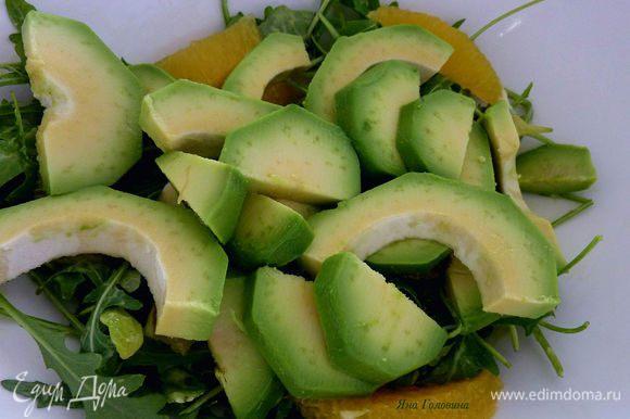 У апельсинов вырезать сегменты и разложить на листья, сверху положить порезанный (плотный ) авокадо.