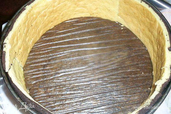 В форму кладем один шоколадный бисквит наверх той стороной, которая была на пергаменте. Устанавливаем бортики из бисквита.