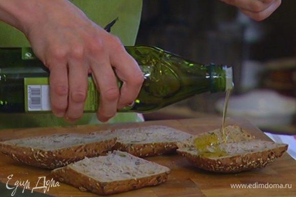 Булочки разрезать вдоль пополам и сбрызнуть половиной оливкового масла.