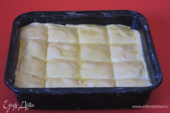 Верхний пласт теста смазать яичным желтком. Разрезать пирог на квадратики.