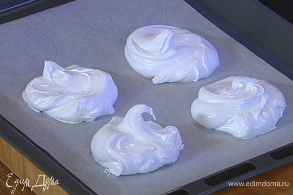 Взбитые белки выложить на бумагу для выпечки, заполняя нарисованные круги.
