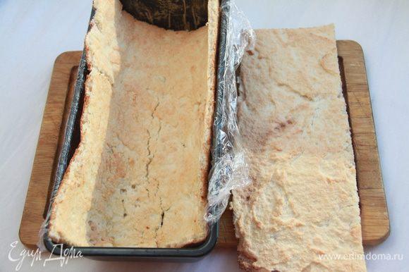 Сразу же разрезать бисквит на 2 части: 1/3 и 2/3 прямоугольника (большая часть будет стенками и должна по размеру подходить к форме, в которой будет собираться торт; меньшая часть - прямоугольник 26х12см. Бисквит быстро твердеет, поэтому необходимо быстро поместить 2/3 части в форму, застеленную пищевой пленкой. Оставшаяся часть будет дном торта.