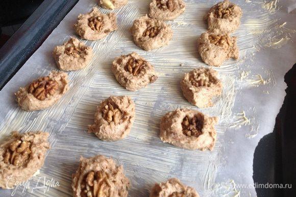 Противень застелите бумагой для выпечки, смажьте маслом. Тесто выложите ложкой на противень и сверху положите половинку грецкого орешка.