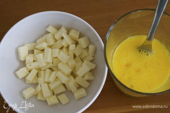 Полумягкий сыр для теста нарезать мелкими кубиками. Два яйца взбить вилкой в стакане.