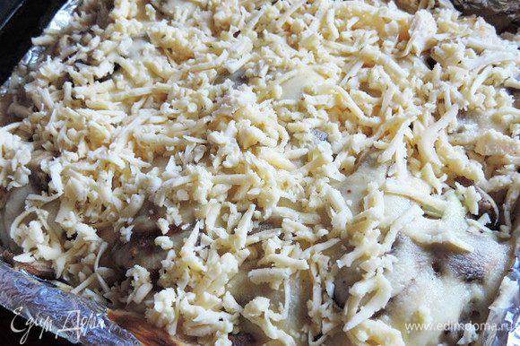 Через 40 минут достаем окорочка и посыпаем их тертым сыром.