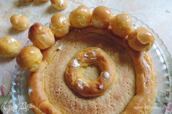 Верхушки наших пироженок обмакиваем в горячую карамель. Затем в карамель окунаем их донышки, можно чайной ложечкой слегка смазывать дно пирожных карамелью и приклеиваем их к внешнему кольцу на корже-основе.