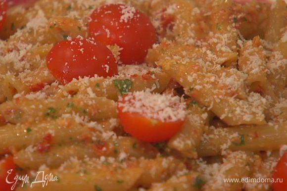 Макароны с песто выложить на тарелку, сверху разложить помидоры, посыпать натертым пармезаном и украсить листьями базилика.