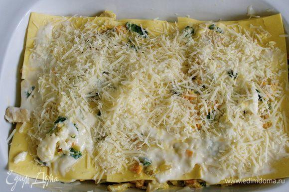 Присыпать тертым сыром пармезан и поставить лазанью запекаться на 20 минут до образования золотистой корочки.