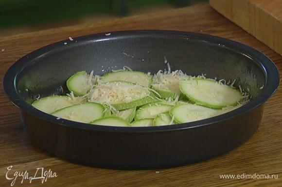Небольшую форму для выпечки смазать оставшимся оливковым маслом, присыпать дно частью натертого сыра, выложить кружки кабачка (можно в форме цветка), немного посыпать сыром и посолить.