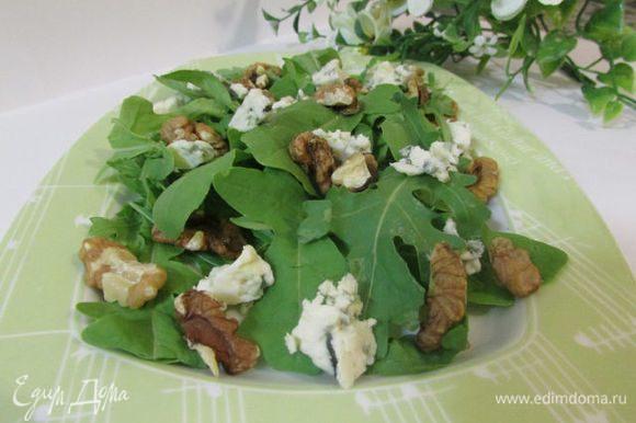 На руколу выложить часть грецких орехов и половину нарезанного мелкими кубиками сыра.
