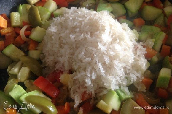 Промять рис. Добавить его к овощам и влить 300 мл. воды.