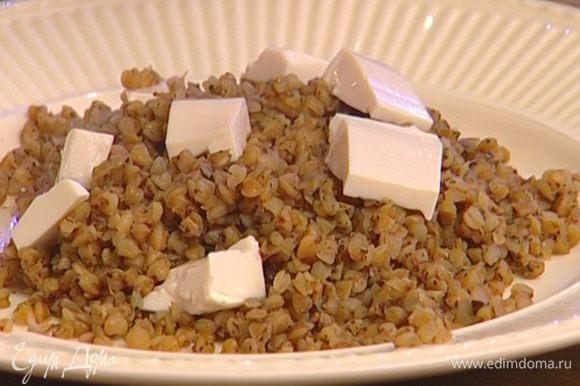 Выложить гречку в тарелки, сверху разложить кусочки тофу, украсить листьями базилика.