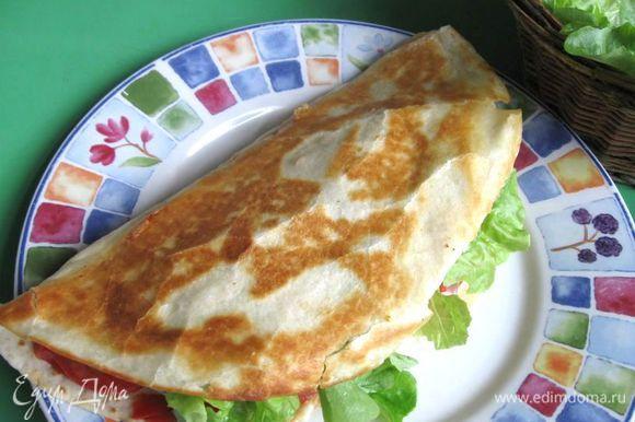 Снять со сковороды с помощью широкой лопаточки, приподнять верхнюю часть и положить листья салата внутрь лепешки.