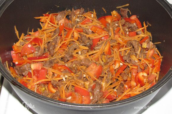Через полтора часа добавить к мясу овощи и измельченный чеснок. Все перемешать и тушить еще пол часа.