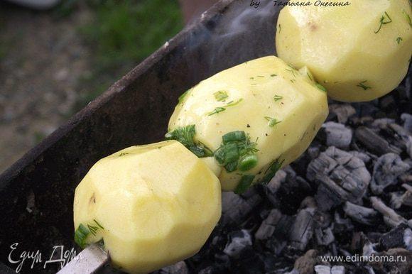 Когда дрова хорошо прогорели, разбиваем угольки. На шампур аккуратно нанизываем картофель и отправляем на мангал. Если картофель не большого размера, нанизываем его целиком, если крупнее - разрезаем пополам.
