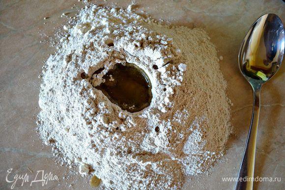 Для приготовления коржей просеять на стол по половине стакана ржаной и пшеничной муки, посолить. Сделать в центре муки лунку и влить в неё оливковое масло.