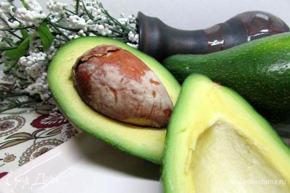 Разрежьте авокадо пополам, проверните половинки в разные стороны и разъедините.