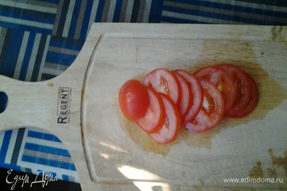 Пока омлет запекается, режем помидор тонкими колечками.