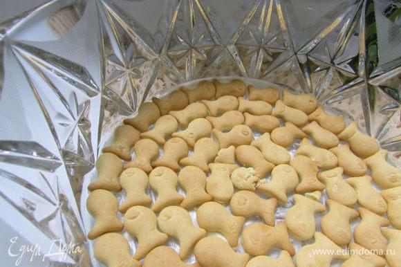 Сборка салата. Дно салатницы слегка смазать майонезом. Выложить в один слой крекер (рыбки).