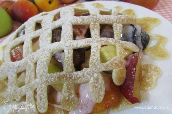 Прикрыть фрукты с йогуртом вторым блинчиком. Посыпать сахарной пудрой.