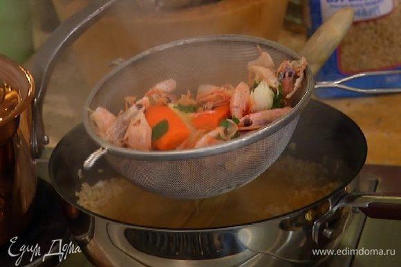Готовый бульон из панцирей процедить, влить в сковороду с рисом и готовить, не накрывая крышкой, около 20 минут до готовности риса. Если бульон выпарится, влить немного горячей воды или белого сухого вина.