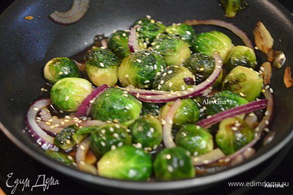 Добавить тонко порезанный красный лук, соевый соус с медом, перемешать. Посыпать кунжутным семенем.