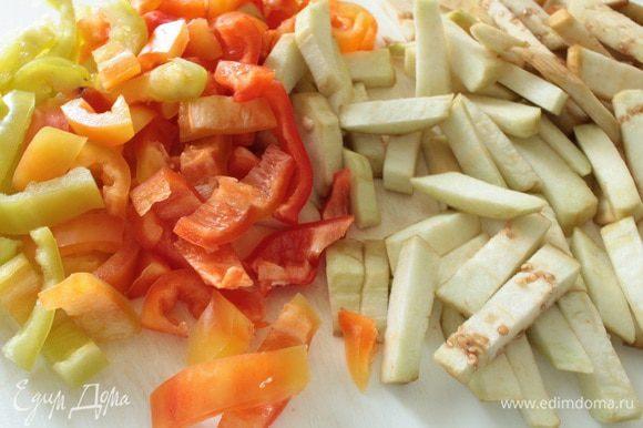Баклажаны почистить,нарезать вдоль пластинами и затем поперек брусочками.У перца удалить семена,нарезать его полосками.