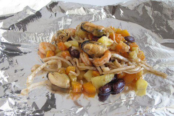 Фольгу сложить в два слоя, придав форму квадрата. Выложить морепродукты с овощами.