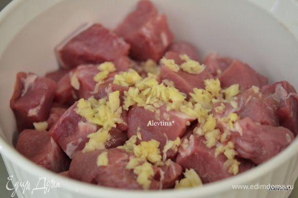 Выложить в глубокую емкость, чеснок порубить мелко, выложить поверх свинины.