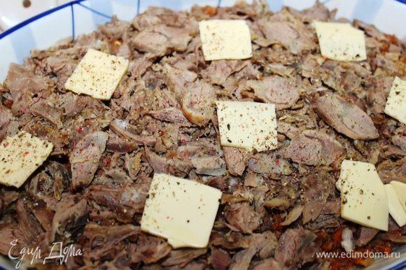 Присыпать еще одной часть сыра (1/4) и выложить нарезанное тонкими пластинками отварное мясо. Сверху разложить остатки сливочного масла (25 грамм), посолить и поперчить.