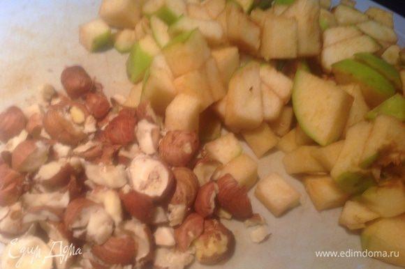 Разогрейте духовку до 170 градусов. Из яблок удалите сердцевину, и мелко порежьте. Фундук порубите.