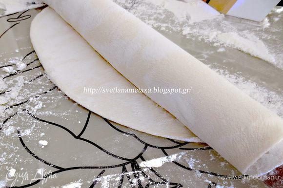 Раскатав тонкий пласт, накручиваем его на скалку и продолжаем раскатывать, руками вытягивая тесто в стороны.