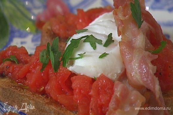 На хлеб выложить измельченные помидоры и яйцо пашот, разделив его пополам, сверху поместить бекон и листья петрушки, все посолить.