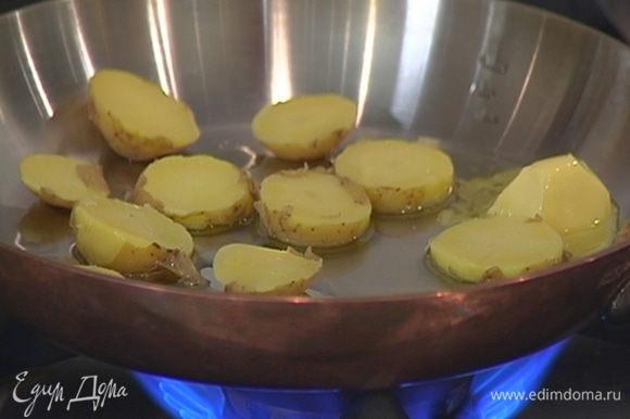 Разогреть в сковороде сливочное и оливковое масло и обжарить ломтики картофеля с двух сторон до золотистой корочки.