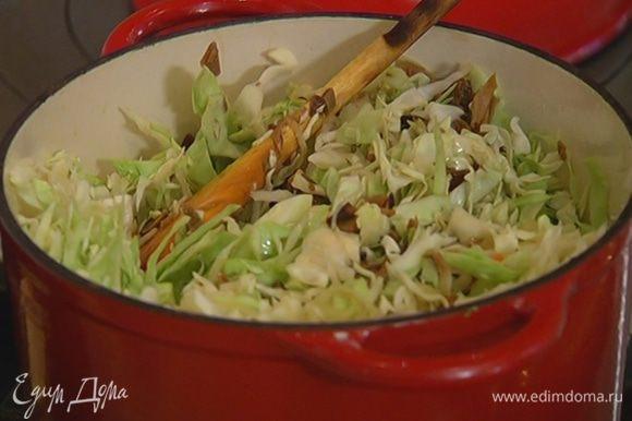 Белое вино влить в кастрюлю с капустой, посолить, добавить сахар и еще раз перемешать.
