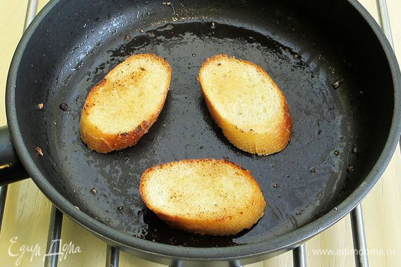 Теперь займемся приготовлением гренок. Багет нарезаем на небольшие ломтики. На сливочном масле обжариваем гренки с двух сторон. Натираем чесноком с солью и посыпаем свежемолотым перцем.
